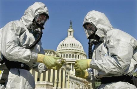 Dos personas con trajes aislantes ante el Capitolio de EEUU