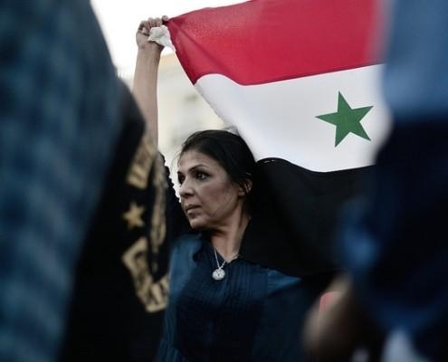 Una mujer porta la bandera de Siria
